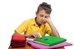 Мальчик при книги смотря пробуренный Все на белой предпосылке Стоковое фото RF