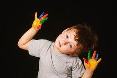 Мальчик при руки покрашенные в ярких цветах, с палитрой в руке Стоковые Фото