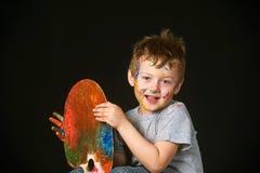 Мальчик при руки покрашенные в ярких цветах, с палитрой в руке Стоковые Изображения