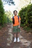 Мальчик при рюкзак и бутылка с водой стоя на пути в лесе Стоковое Фото