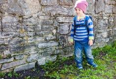 Мальчик при рюкзак стоя около каменной стены Стоковые Фотографии RF