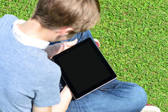 Мальчик при сенсорная панель сидя на луге Стоковое Изображение RF