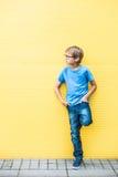 Мальчик при стекла стоя около желтых oudoors стены Стоковая Фотография