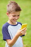 Мальчик при smartphone играя игру в парке лета Стоковая Фотография RF