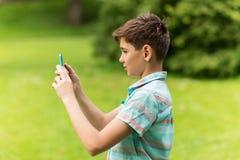 Мальчик при smartphone играя игру в парке лета Стоковое Фото