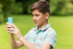 Мальчик при smartphone играя игру в парке лета Стоковое Изображение RF
