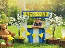 Мальчик продавая желтый лимонад на стойке