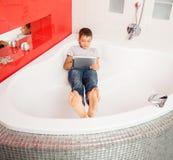 Мальчик пряча в ванной комнате, играя в таблетке Стоковые Изображения