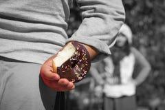 Мальчик пряча donuts шоколада за его назад стоковое изображение rf