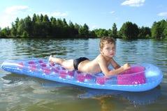 Мальчик плавает в реке. Стоковая Фотография