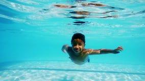 Мальчик плавая под водой в бассейне видеоматериал