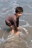 мальчик пляжа играя детенышей Стоковые Фото