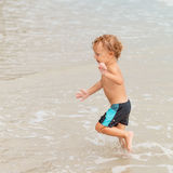 мальчик пляжа немногая играя стоковое фото rf