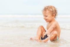 мальчик пляжа немногая играя стоковая фотография