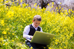 Мальчик работая на компьтер-книжке Стоковое Изображение