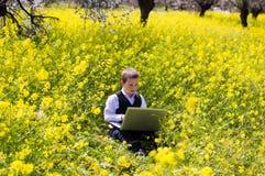 Мальчик работая на компьтер-книжке Стоковая Фотография