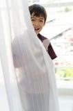 Мальчик раскрывая занавес двери Стоковые Изображения RF