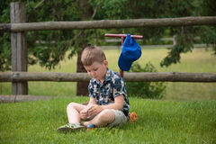 Мальчик рассматривая камешек Стоковая Фотография