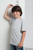 Мальчик растя высокорослый и измеряя Стоковые Изображения RF