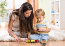 Мальчик ребенка играя с игрушками внутри помещения дома Стоковая Фотография