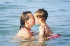 Мальчик ребенка матери и сына играя обнимать в подныривании воды в океане моря Стоковые Фото