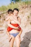 Мальчик ребенка матери и сына играя обнимать на пляже песка около океана моря Стоковая Фотография RF