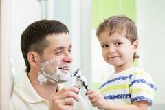Мальчик ребенка пытаясь побрить как его папа стоковое изображение rf