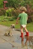 Мальчик, ребенок в красном резиновом Wellingtons, разговаривая с щенком Детство в пеленках Стоковое Изображение