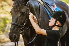 Мальчик седлая лошадь и затягивает распорку Передний план Стоковая Фотография RF