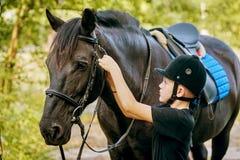 Мальчик седлая лошадь и затягивает распорку Передний план Стоковые Изображения RF