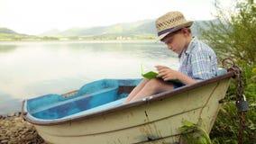 Мальчик сидит в причаленный на шлюпке банка читая книгу сток-видео