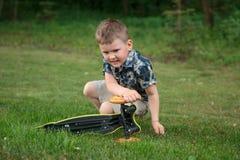 Мальчик сидит и ремонтирует самокат стоковая фотография
