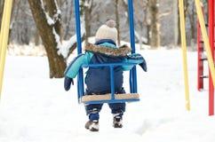 Мальчик сидит на качании, вид сзади зимнего дня прекрасной погоды Стоковое фото RF
