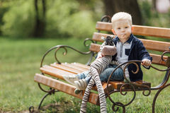 Мальчик сидит на стенде с его игрушкой Стоковые Изображения