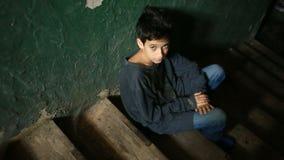 Мальчик сидит на шагах покинутого крылечка Концепция наркомании ` s детей, vagrancy, беспризорности видеоматериал