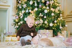 Мальчик сидит под рождественской елкой Стоковые Изображения RF