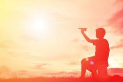 Мальчик силуэта держа бумажную ракету Стоковые Изображения RF