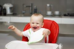 Мальчик сидя в высоком стуле и смеяться над стоковая фотография