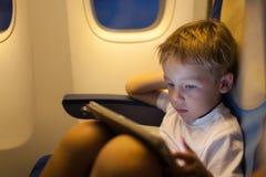 Мальчик сидя в плоскости и используя ПК таблетки стоковое изображение