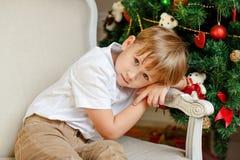Мальчик сидя в стуле и унылый на рождестве Стоковые Фото