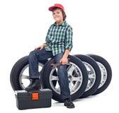 Мальчик сидя на автошинах автомобиля стоковое изображение