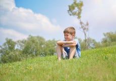 Мальчик сидя на зеленом холме природы снаружи Стоковые Изображения RF
