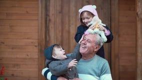 Мальчик сидя на коленях деда, девушка стоя задний и объятие Брат и сестра играя при овцы игрушки, смеясь над 4K Стоковое Изображение