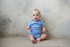 Мальчик сидя на поле около стены Стоковое Фото