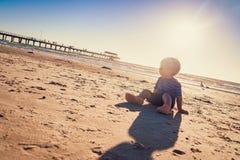 Мальчик сидя на пляже Стоковые Фото
