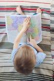 Мальчик сидя на софе и указывая на карту Стоковое Изображение RF