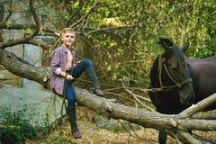 Мальчик сидя на старом дереве представляя с лошадью после разминки Фокус на мальчике Стоковое Изображение RF