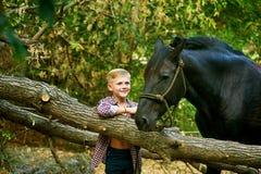 Мальчик сидя на старом дереве представляя с лошадью после разминки Фокус на мальчике Стоковое Фото