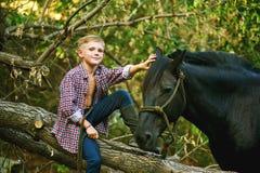 Мальчик сидя на старом дереве представляя с лошадью после разминки Фокус на мальчике Стоковые Фото