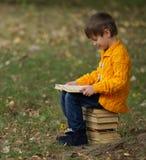 Мальчик сидя на стоге книг стоковые фото